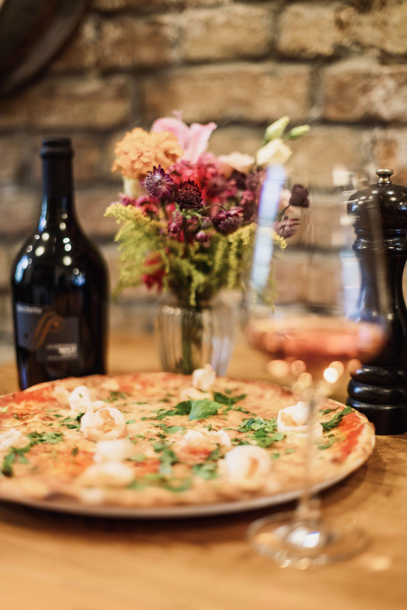 Cantinetta italienische Steinofenpizza mit einem Glas Rosé